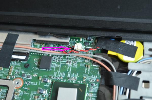 什么样的情况下会需要拆键盘呢? 一般来说清理风扇的时候而且不想彻底将风扇拆卸下来的时候可以在这里完成,因为可以看到一点点的风扇叶子,一共只有两个螺丝看到下面图中有两个蓝色的圈拧开后 我们就可以看到后盖的下面有一个固定键盘的螺丝另外一个我们也用箭头标注了起来,完成上面的动作后再将T420的屏幕打开和其他的一些IBM机型一样将键盘往前推然后取出就可以了。    图中应该可以看到键盘的数据排线前面有一个小的塑料多出来,这里就是用来给拆排线的把手,我们拉着她就可以将它与主板分离,另外你要注意拆的时候这里有一个大的